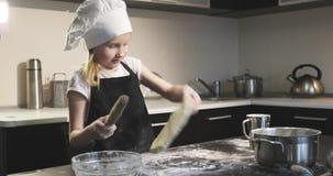 Ένας μικρός μάγειρας κοριτσιών σε μια ποδιά και μια ΚΑΠ ξεδιπλώνει τη ζύμη φιλμ μικρού μήκους