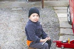 Ένας μικρός μηχανικός που επισκευάζει ένα αυτοκίνητο Στοκ Φωτογραφίες