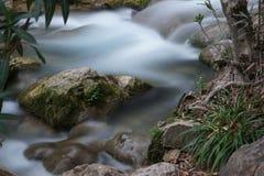 Ένας μικρός τρέχων κολπίσκος με τα ορμητικά σημεία ποταμού και μια πέτρα με το βρύο που προεξέχει από το νερό στοκ εικόνες