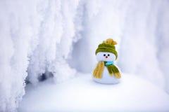 Ένας μικρός χιονάνθρωπος σε ένα καπέλο και ένα μαντίλι Στοκ Φωτογραφίες