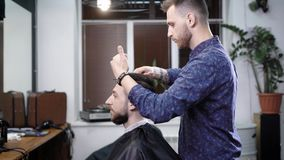 Ένας μοντέρνος κομμωτής κτενίζει ήπια την τρίχα πελατών του ` s προκειμένου να δημιουργηθεί ένα μοντέρνο hairstyle σε ένα σαλόνι  φιλμ μικρού μήκους