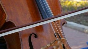 Ένας μουσικός οδών παίζει το βιολοντσέλο πυροβοληθείσα κινηματογράφηση σε πρώτο πλάνο 4K φιλμ μικρού μήκους