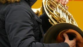 Ένας μουσικός οδών που παίζει το γαλλικό κέρατο κοντά επάνω βλέπει φιλμ μικρού μήκους