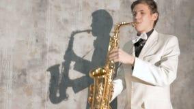 Ένας μουσικός σε ένα άσπρο κοστούμι παίζει το saxophone Αποδίδει σε ένα νυχτερινό κέντρο διασκέδασης, σε ένα γκρίζο κλίμα Κινηματ απόθεμα βίντεο