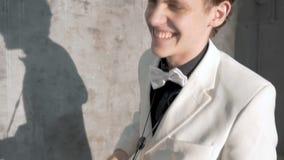 Ένας μουσικός σε ένα άσπρο κοστούμι παίζει το saxophone Αποδίδει σε ένα νυχτερινό κέντρο διασκέδασης, σε ένα γκρίζο κλίμα Κινηματ φιλμ μικρού μήκους