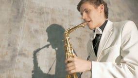 Ένας μουσικός σε ένα άσπρο κοστούμι παίζει το saxophone Κινηματογράφηση σε πρώτο πλάνο φιλμ μικρού μήκους