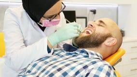 Ένας μουσουλμανικός θηλυκός οδοντίατρος που εργάζεται στα δόντια ασθενών, ο ασθενής εξετάζει τη κάμερα και χαμογελά απόθεμα βίντεο