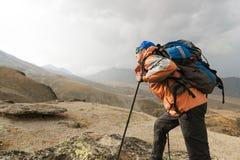 Ένας μόνος τουρίστας απολαμβάνει τα τοπία υψηλά στα βουνά όπου δεν υπάρχει καμία χλόη του χωριού και του χιονιού Στοκ Εικόνα