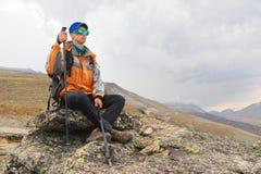 Ένας μόνος τουρίστας με ένα σακίδιο πλάτης και στα γυαλιά ηλίου στηρίζεται τη συνεδρίαση σε έναν βράχο Στοκ Εικόνα