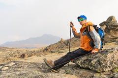 Ένας μόνος τουρίστας με ένα σακίδιο πλάτης και στα γυαλιά ηλίου στηρίζεται τη συνεδρίαση σε έναν βράχο Στοκ εικόνες με δικαίωμα ελεύθερης χρήσης
