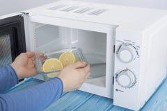 Ένας νέος άσπρος φούρνος μικροκυμάτων, σε μια μπλε ξύλινη επιφάνεια για τη θέρμανση στοκ φωτογραφίες