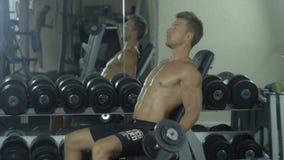Ένας νέος αθλητής συμμετέχει ενεργά στις αθλητικές ασκήσεις γιατί παραδίδει την αίθουσα, εκπαιδευτικός τους μυς των χεριών απόθεμα βίντεο