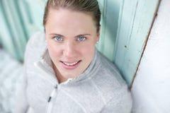 Ένας νέος αθλητής στέκεται μπροστά από μια τυρκουάζ πόρτα ανατρέχοντας στη κάμερα Στοκ εικόνες με δικαίωμα ελεύθερης χρήσης