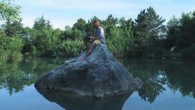 Ένας νέος ανεξάρτητος τύπος κάθεται σε μια πέτρα στη μέση μιας λίμνης με ένα lap-top Ανεξάρτητη έννοια Εργασία για το ταξίδι Ασύρ απόθεμα βίντεο
