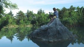 Ένας νέος ανεξάρτητος τύπος κάθεται σε μια πέτρα στη μέση μιας λίμνης με ένα lap-top Ανεξάρτητη έννοια Εργασία για το ταξίδι Ασύρ φιλμ μικρού μήκους