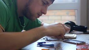 Ένας νέος αρσενικός μάγος που στιχουργείται στις μικρές λεπτομέρειες του σπασμένου τηλεφώνου, θέλει να το επισκευάσει 3840x2160 4 φιλμ μικρού μήκους