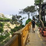 Ένας νέος αρσενικός τουρίστας που περπατά κατά μήκος ενός patio με τα εστιατόρια υψηλά στοκ φωτογραφία με δικαίωμα ελεύθερης χρήσης