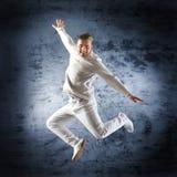 Ένας νέος αρσενικός χορευτής που αποδίδει στα άσπρα ενδύματα Στοκ Φωτογραφίες