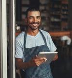 Ένας νέος αφρικανικός επιχειρηματίας καφέδων που κρατά την ψηφιακή ταμπλέτα στοκ φωτογραφία