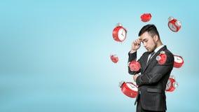 Ένας νέος γενειοφόρος επιχειρηματίας βαθιά στη σκέψη ενώ πολλά κόκκινα αναδρομικά ξυπνητήρια που πετούν γύρω από τον στοκ εικόνα