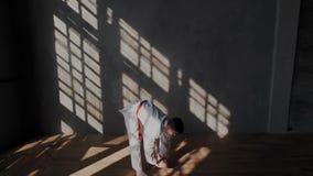 Ένας νέος γενναίος και ισχυρός αθλητικός τύπος προετοιμάζεται για μια μονομαχία taekwondo Άσπρο κιμονό με μια κόκκινη ζώνη, ξυπόλ απόθεμα βίντεο