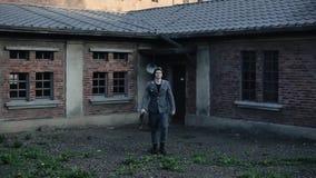 Ένας νέος γερμανικός στρατιώτης που περπατά προς τη κάμερα με ένα τούβλινο σπίτι στο υπόβαθρο WW2 αναπαράσταση φιλμ μικρού μήκους