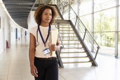 Ένας νέος γιατρός με το στηθοσκόπιο, που περπατά στο σύγχρονο λόμπι στοκ εικόνα