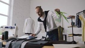Ένας νέος δημιουργικός ράφτης κάνει τις μετρήσεις ενός άσπρου σακακιού σε ένα ομοίωμα στο στούντιό του για το ράψιμο των ενδυμάτω απόθεμα βίντεο