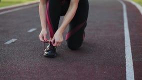 Ένας νέος δρομέας κοριτσιών ικανότητας sportswear στα τρεξίματα κατά μήκος της πορείας, κατόπιν σταματά το δεσμό τα κορδόνια Κατό φιλμ μικρού μήκους