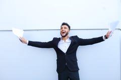 Ένας νέος ενήλικος αραβικός επιχειρηματίας που χαμογελά ευρέως και κρατά pape Στοκ Φωτογραφία