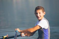Ένας νέος ενιαίος κωπηλατώντας ανταγωνιστής scull κωπηλατεί στην ήρεμη λίμνη Στοκ Φωτογραφίες