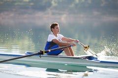 Ένας νέος ενιαίος κωπηλατώντας ανταγωνιστής scull κωπηλατεί στην ήρεμη λίμνη Στοκ φωτογραφίες με δικαίωμα ελεύθερης χρήσης