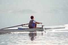 Ένας νέος ενιαίος κωπηλατώντας ανταγωνιστής scull κωπηλατεί στην ήρεμη λίμνη Στοκ Φωτογραφία
