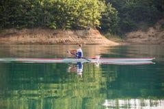 Ένας νέος ενιαίος κωπηλατώντας ανταγωνιστής scull κωπηλατεί στην ήρεμη λίμνη Στοκ εικόνες με δικαίωμα ελεύθερης χρήσης