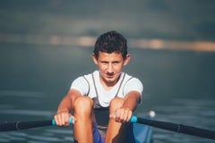 Ένας νέος ενιαίος κωπηλατώντας ανταγωνιστής scull κωπηλατεί στην ήρεμη λίμνη Στοκ Εικόνα