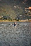 Ένας νέος ενιαίος κωπηλατώντας ανταγωνιστής scull κωπηλατεί στην ήρεμη λίμνη Στοκ εικόνα με δικαίωμα ελεύθερης χρήσης