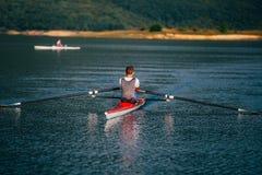 Ένας νέος ενιαίος κωπηλατώντας ανταγωνιστής scull κωπηλατεί στην ήρεμη λίμνη Στοκ Εικόνες