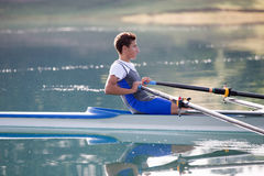 Ένας νέος ενιαίος κωπηλατώντας ανταγωνιστής scull κωπηλατεί στην ήρεμη λίμνη Στοκ φωτογραφία με δικαίωμα ελεύθερης χρήσης