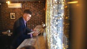 Ένας νέος επιχειρηματίας εργάζεται σε έναν καφέ με ένα lap-top απόθεμα βίντεο