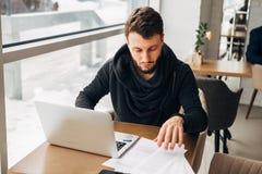 Ένας νέος επιχειρηματίας εργάζεται σε έναν καφέ με ένα lap-top Στοκ Φωτογραφία