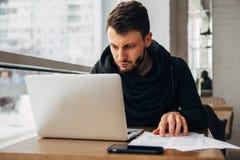 Ένας νέος επιχειρηματίας εργάζεται σε έναν καφέ με ένα lap-top Στοκ Εικόνες