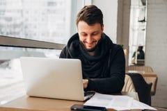 Ένας νέος επιχειρηματίας εργάζεται σε έναν καφέ με ένα lap-top Στοκ εικόνα με δικαίωμα ελεύθερης χρήσης