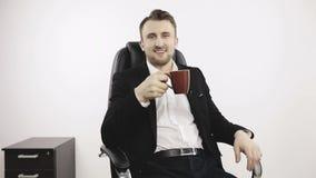 Ένας νέος επιχειρηματίας πίνει τον καφέ στο γραφείο φιλμ μικρού μήκους