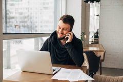 Ένας νέος επιχειρηματίας που μιλά στο τηλέφωνο και που εργάζεται σε ένα lap-top σε έναν καφέ Στοκ φωτογραφία με δικαίωμα ελεύθερης χρήσης