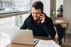 Ένας νέος επιχειρηματίας που μιλά στο τηλέφωνο και που εργάζεται σε ένα lap-top σε έναν καφέ Στοκ εικόνες με δικαίωμα ελεύθερης χρήσης