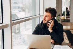 Ένας νέος επιχειρηματίας που μιλά στο τηλέφωνο και που εργάζεται σε ένα lap-top σε έναν καφέ Στοκ Φωτογραφίες