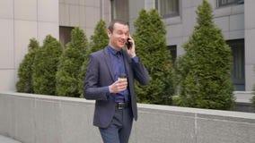 Ένας νέος επιχειρηματίας που περπατά κάτω από την οδό και επικοινωνεί ευτυχώς στο τηλεφώνημα φιλμ μικρού μήκους