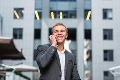 Ένας νέος επιχειρηματίας που στέκεται στα βήματα ενός κτιρίου γραφείων, με έναν φάκελλο των εγγράφων και του ποδηλάτου Νέο όμορφο Στοκ Φωτογραφία