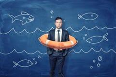 Ένας νέος επιχειρηματίας στέκεται μέσα σε έναν πορτοκαλή σημαντήρα ζωής σε ένα μπλε υπόβαθρο με τα κύματα και τα ψάρια κιμωλίας στοκ φωτογραφία με δικαίωμα ελεύθερης χρήσης
