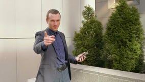 Ένας νέος επιχειρηματίας στέκεται στην οδό δείχνοντας το δάχτυλό του στη κάμερα απόθεμα βίντεο